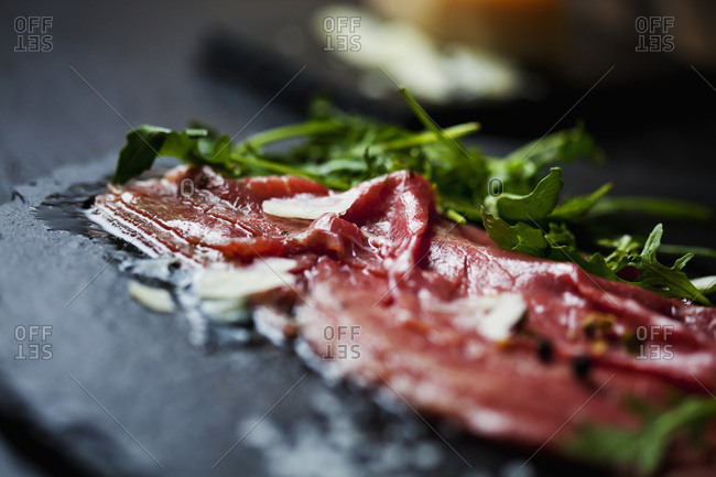 Beef Carpaccio with rocket- olive oil- parmesan- pepper and salt on slate