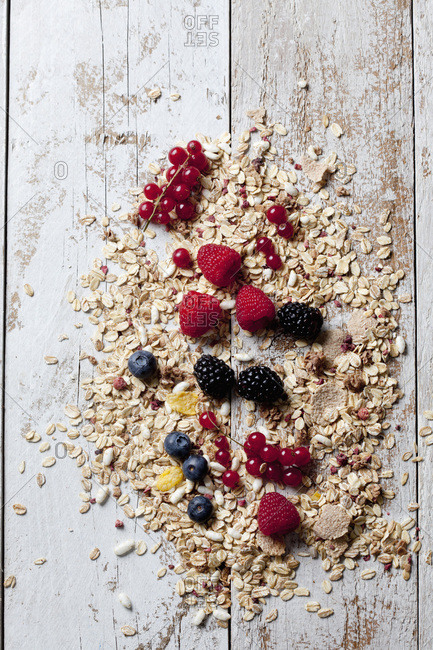 Granola with various wild berries on wood