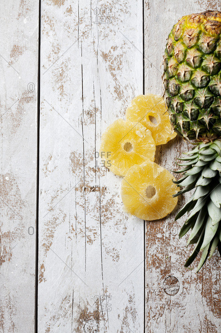 Pineapple and dried rings of pineapple on wood