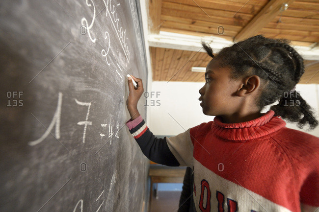 Madagascar- Girl in Fianarantsoa elementary school calculating at blackboard