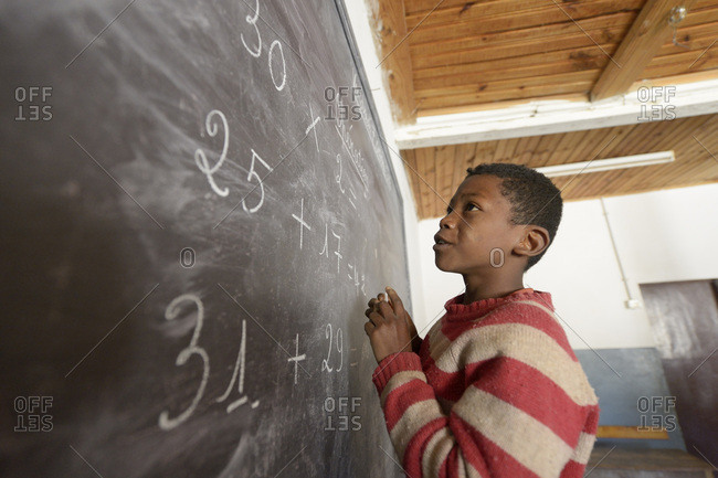 Madagascar- Boy in Fianarantsoa elementary school calculating at blackboard