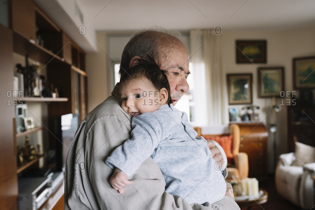 Great-grandfather holding baby at home