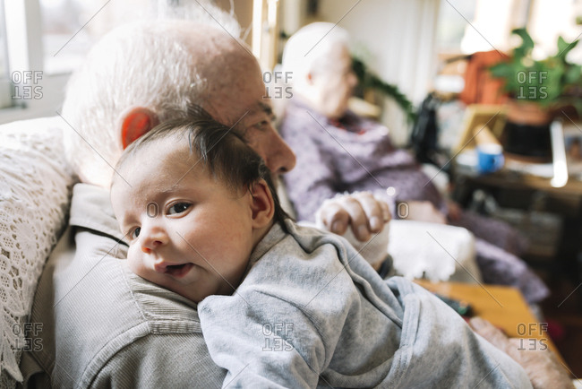 Great-grandfather holding baby at home with his wife in background