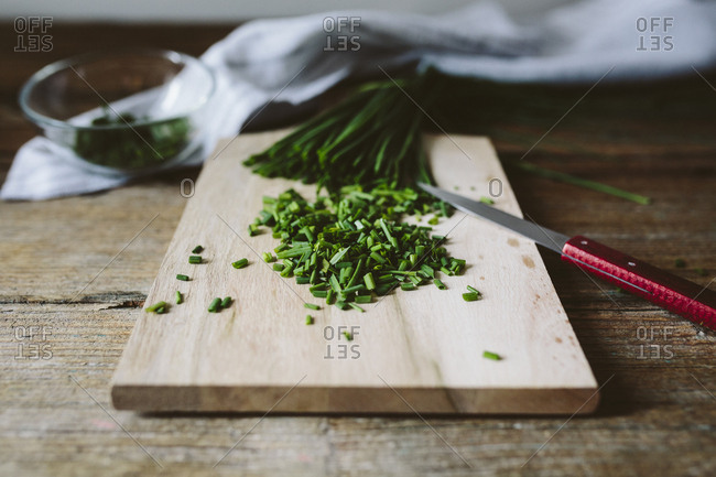 Chopped and whole chives and kitchen knife on wooden board