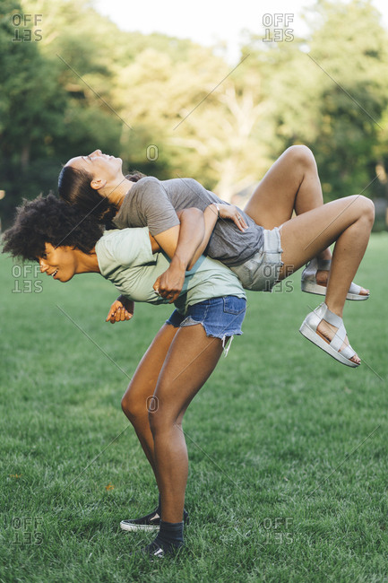 Young woman carrying her best friend piggyback in a park