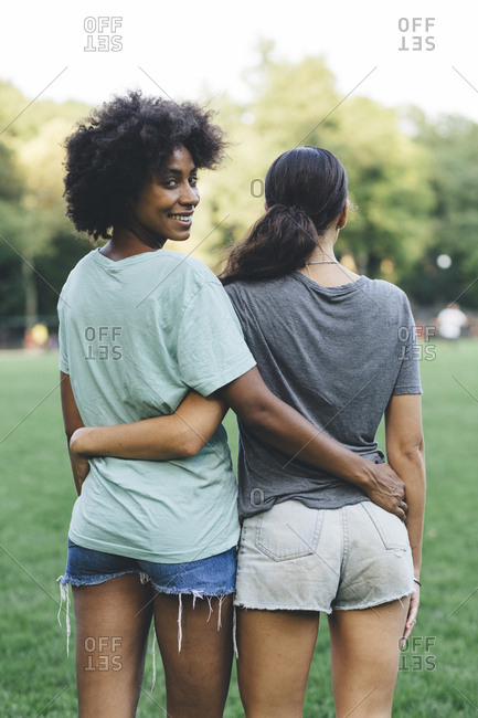 Two women arm in arm in a park