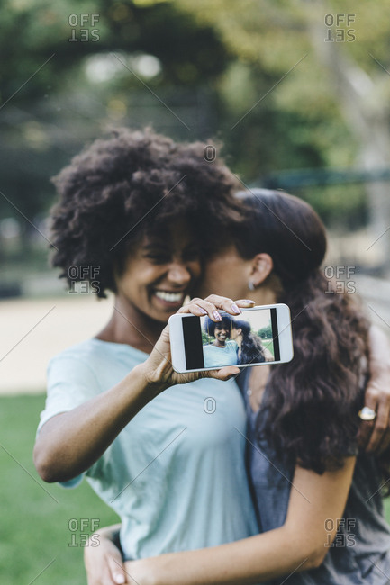 Two women taking selfie with smartphone in a park