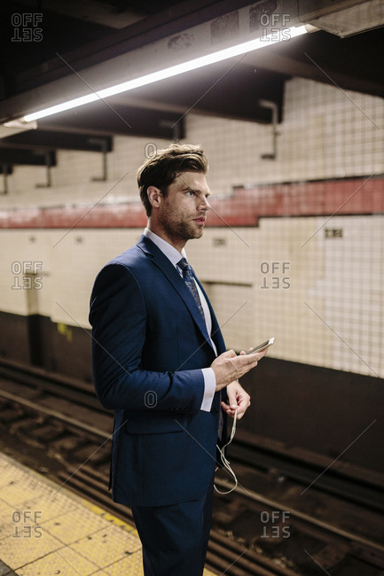 Businessman standing at a New York metro station using smart phone
