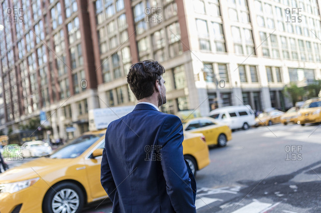 Businessman in the streets of Manhattan with yellow cab in background