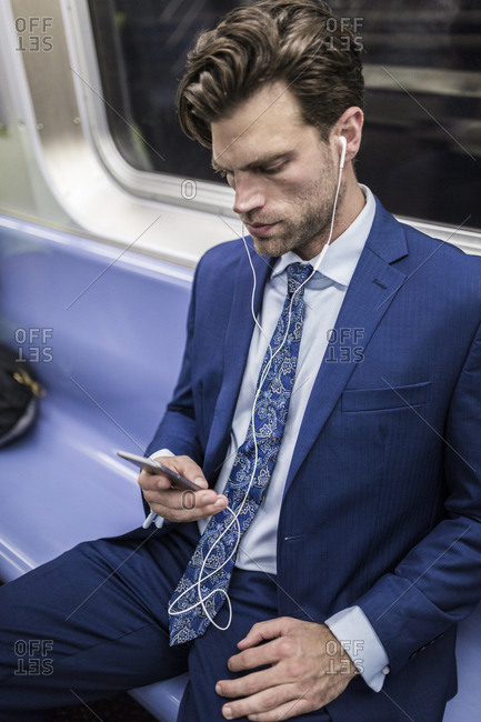 Businessman in metro using smart phone