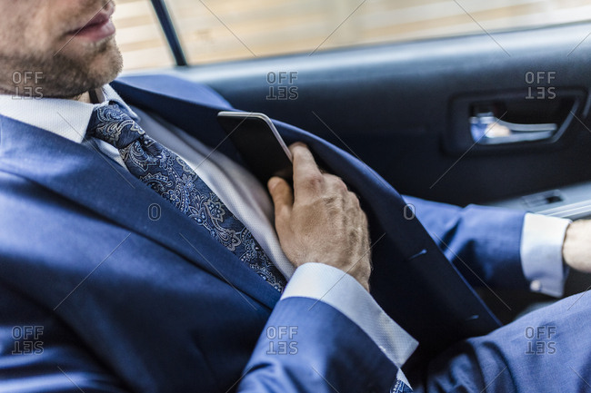 Businessman sitting in taxi- using smart phone