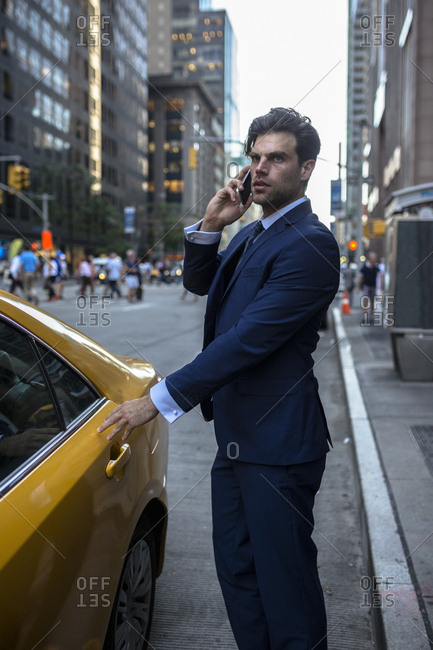 Businessman on the phone entering yellow taxi in Manhattan