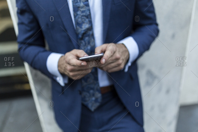 Businessman leaning on a wall in the city- using smart phone