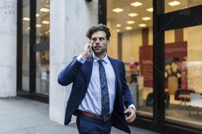 Handsome businessman in a hurry running through Manhattan- using smart phone
