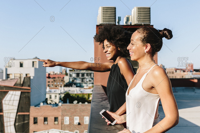 Female friends standing on rooftop- pointing at distance