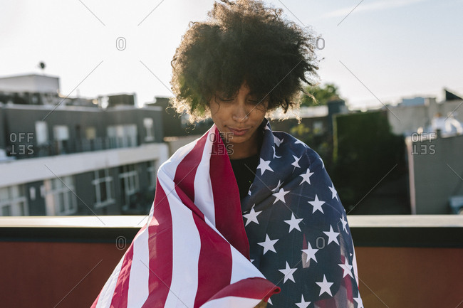 Young woman standing on rooftop warped in US American flag
