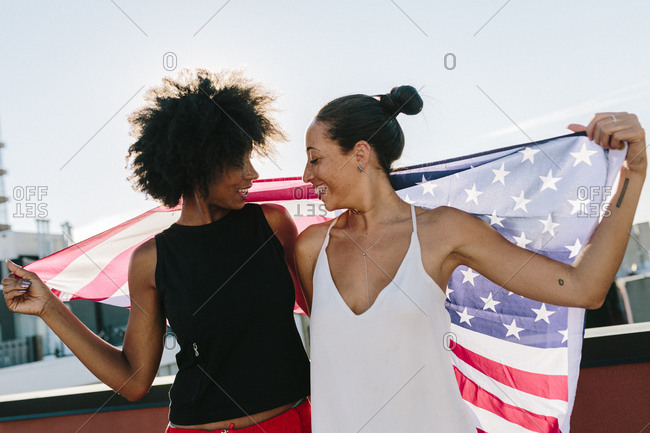 Female friends holding US American flag- standing on rooftop