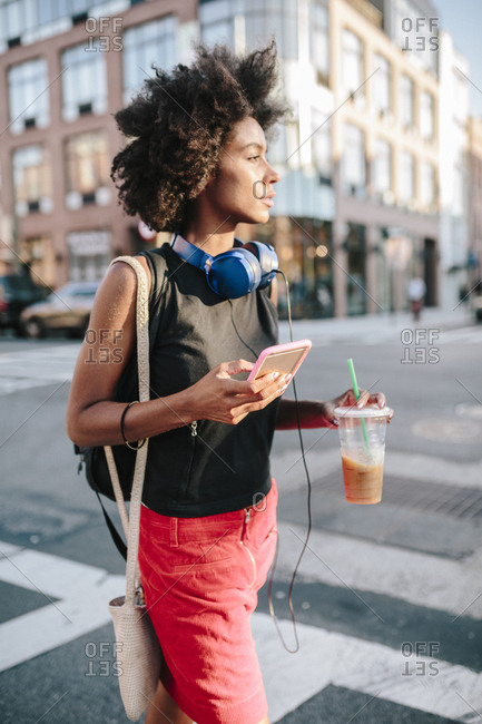 Young woman with headphones and smart phone crossing street in Brooklyn- carrying take away drink