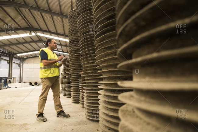 Worker in concrete factory inspecting metal tubes