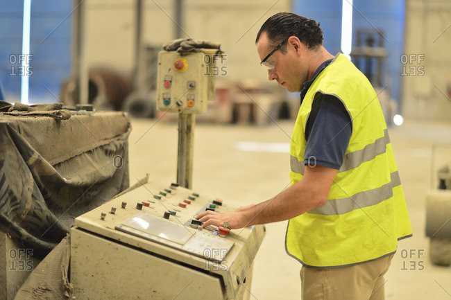 Worker in concrete factory pressing button on control panel