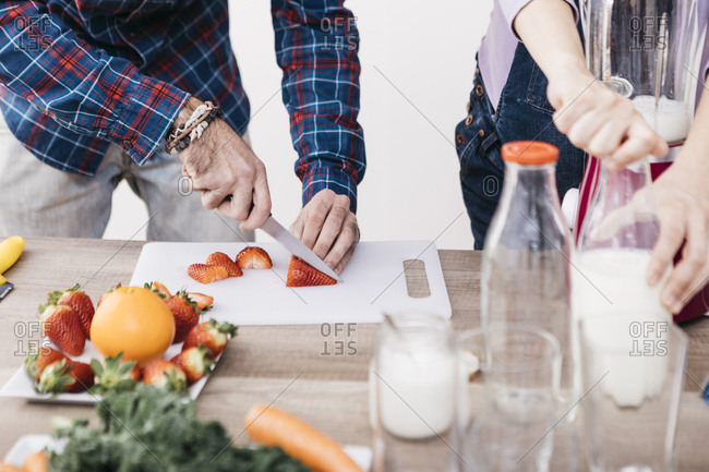 Couple preparing smoothies with fresh fruits and vegetables- partial view