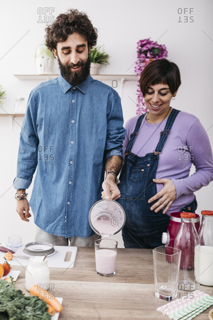 Couple pouring prepared fruit smoothie into a glass