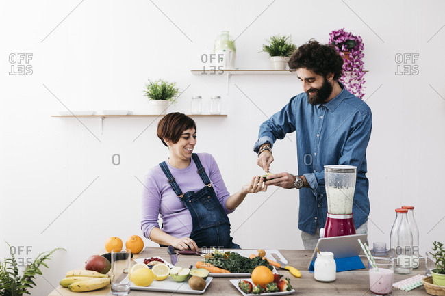 Smiling couple preparing healthy smoothies with fresh fruits and vegetables
