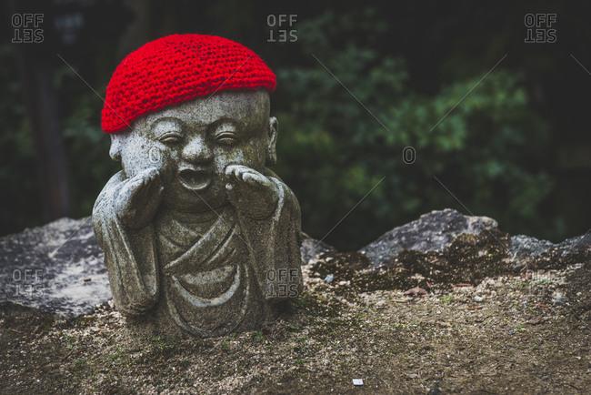 Japan- Miyajima- Danish-In Temple- stone Buddha with crocheted skullcaps
