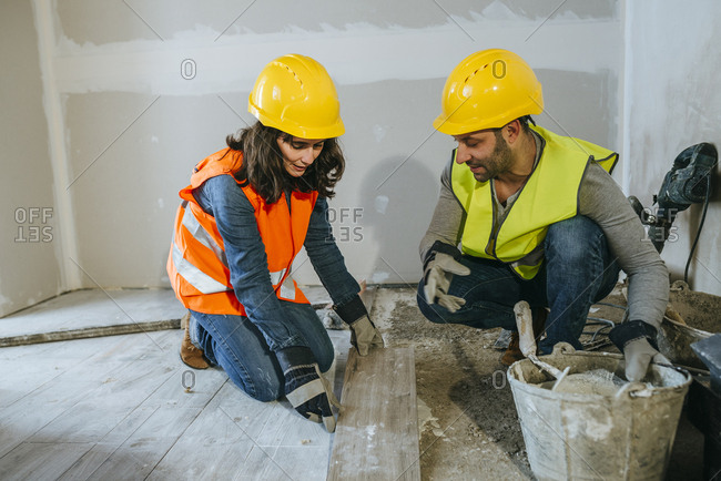 Male and female construction worker placing flooring