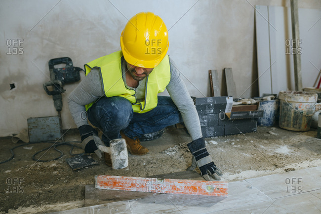 Construction worker placing flooring with a mallet