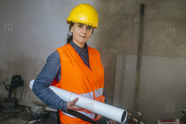 Woman wearing hard hat and reflective vest on construction site holding blueprint