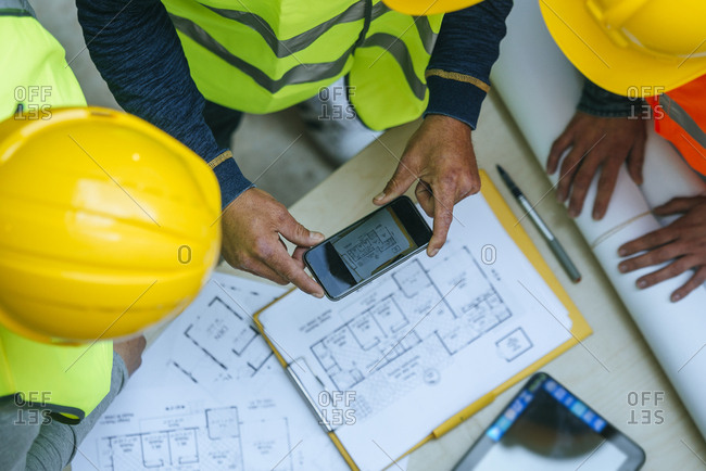 Woman and two men in work wear taking cell phone picture of a construction plan