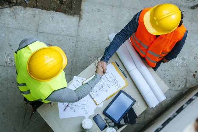 Woman and man in work wear shaking hands above construction plan