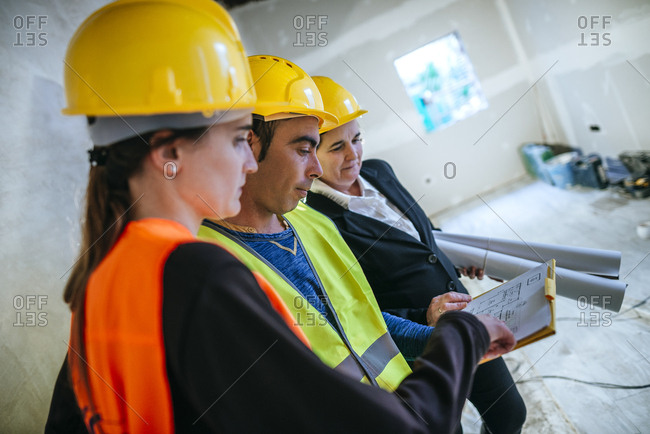 Two women and construction worker on construction site looking at plan