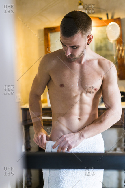 Young man with bare chest wrapping towel around his hips