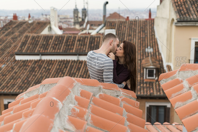 Amorous couple sitting on rooftop- kissing and embracing