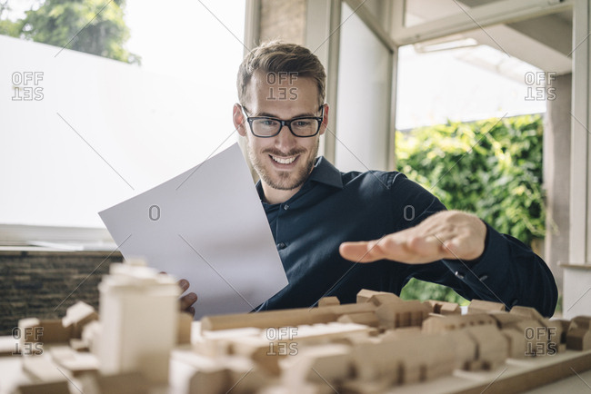 Smiling architect looking at urban development model