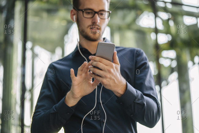 Businessman holding smartphone with connected earphones