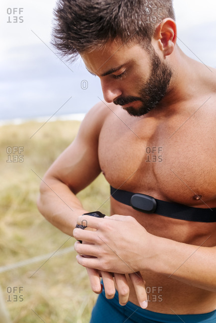 Bare-chested athlete outdoors looking on smart watch