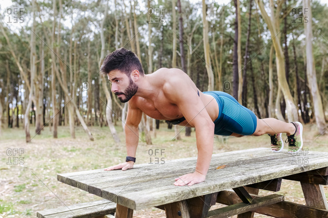Bare-chested man doing push-ups on wooden table outdoors