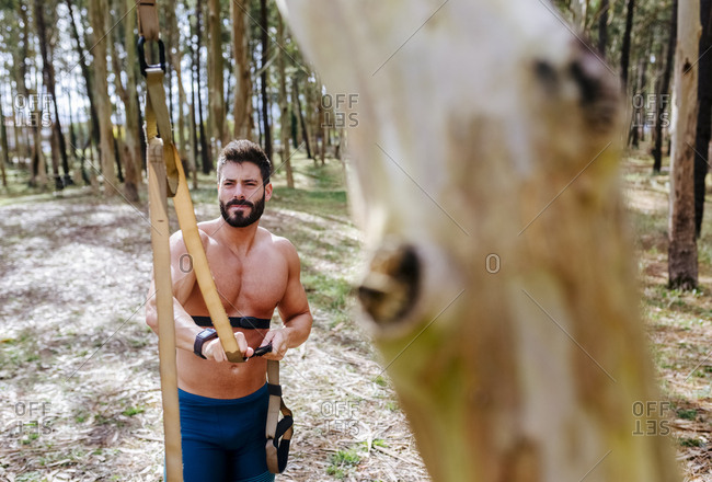 Bare-chested man preparing suspension training outdoors