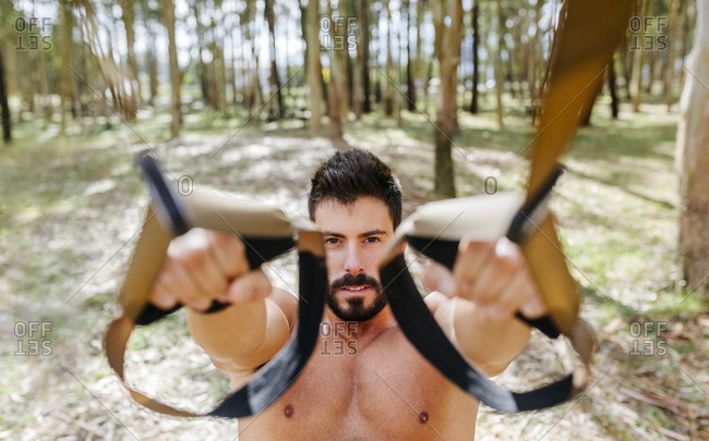 Bare-chested man doing suspension training outdoors