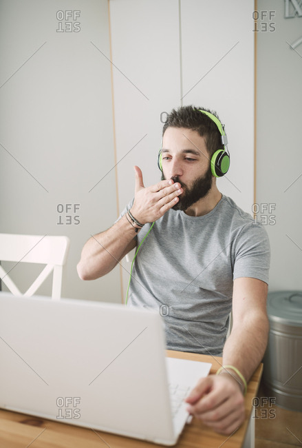 Young man wearing headphones- using laptop and blowing a kiss