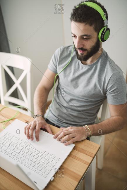 Young man wearing headphones- using laptop