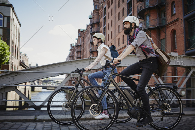 Germany- Hamburg- couple riding electric bicycles at Old Warehouse District