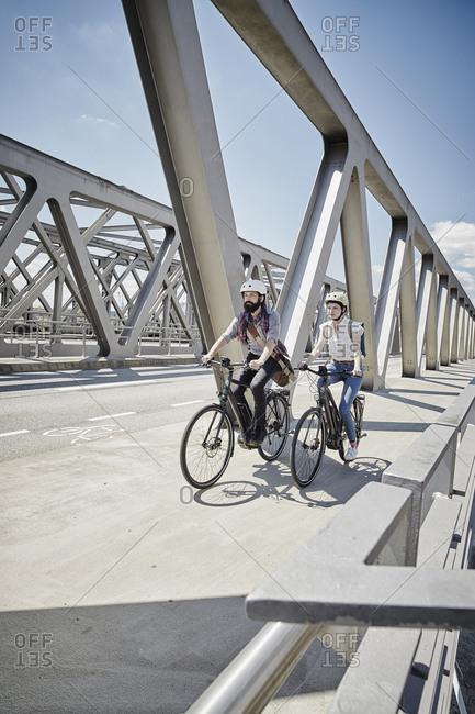 Germany- Hamburg- couple riding electric bicycles on a bridge
