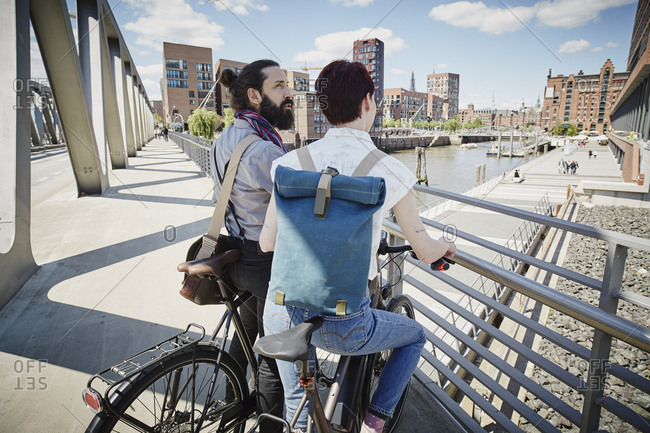 Germany- Hamburg- couple with electric bicycles on a bridge