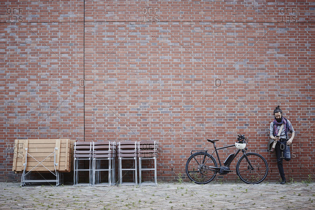 Man with electric bicycle leaning against brick wall looking at cell phone