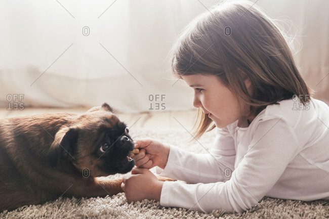 Little girl lying on the carpet with her dog at home