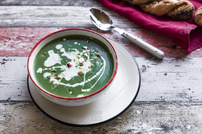Bowl of spinach soup with chili pods and almonds
